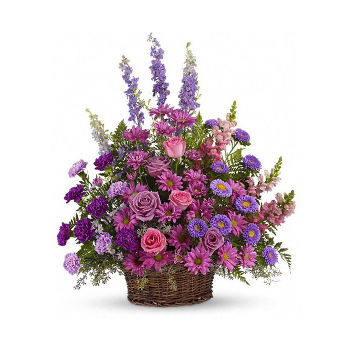 Purple, pink and lavender petals abound in a lovely mix of flowers such as roses, carnations, snapdragons, larkspur, matsumoto and monte cassino asters, nestled among leatherleaf fern and eucalyptus in a round wicker basket.